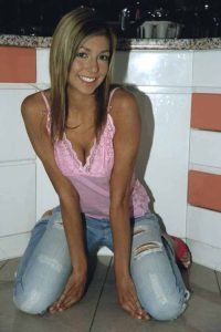 Gail kneeing on kitchen floor in pink top and blue jeans.