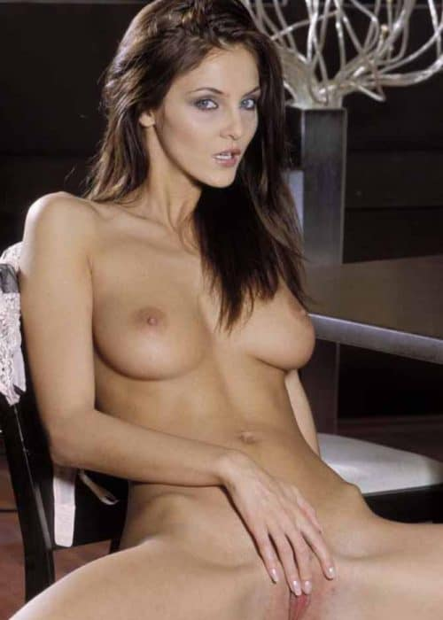 Hazel sitting fully nude in chair, legs spread while holding herself.