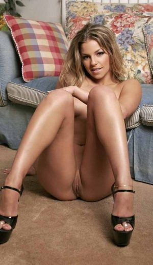 Lara sitting against couch spreading her legs fully nude.