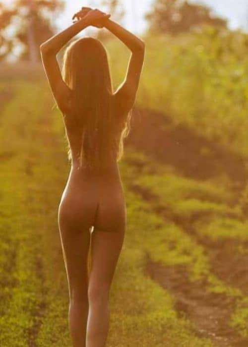 Kayley fully nude walking outside with hands above her head.
